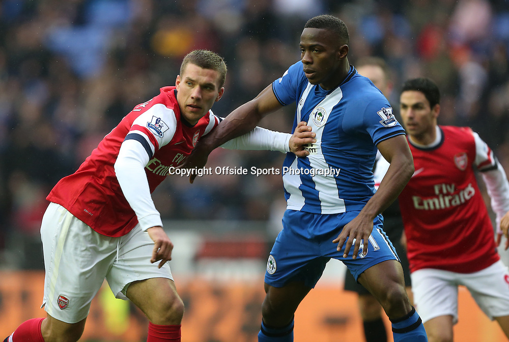 22nd December 2012 - Barclays Premier League - Wigan Athletic vs. Arsenal - Lukas Podolski of Arsenal tussles with Maynor Figueroa of Wigan - Photo: Simon Stacpoole / Offside.