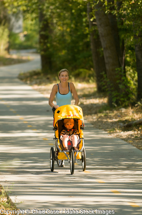 Idaho, Boise Greenbelt that runs along the Boise River . Mother running with kids in stroller