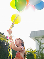 Girl holding bunch of balloons looking up smilig