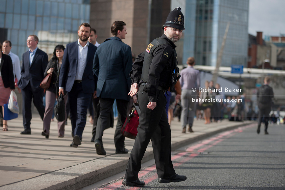 36 hours after the London Bridge and Borough Market terrorist attack, the capital returns to normality and Londoners return to their first day to work and a very visible police presence is evident, on Monday 5th June 2017, in the south London borough of Southwark, England. 17 people were killed and many others left with life-changing injuries - but the British spirit of defiance and to carry on with every day life, endures.