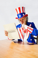 Uncle Sam sitting at a table holding a hand to his head in worry and surprise while looking at the United States Deficit.