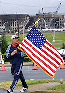 A 9.21 MG IMAGE OF:Arlington, VA 9/14/01 A man with his flag walks to a hill near the Pentagon to observe a moment of Silence at noon 9/14/01  photo by Dennis Brack