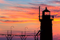 The setting sun lends it fire to clouds over South Haven, Michigan's lighthouse