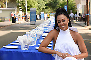 Actress Tia Mowry sits at a 2,000 foot table holding over 6,000 dishes at the Family Dinner with Dawn event in Lambertville, NJ, Sunday, Aug. 13, 2017, to demonstrate how one 21.6 oz bottle of Dawn can wash an entire town's dishes. (Photo by Diane Bondareff/Invision for Dawn/AP Images)