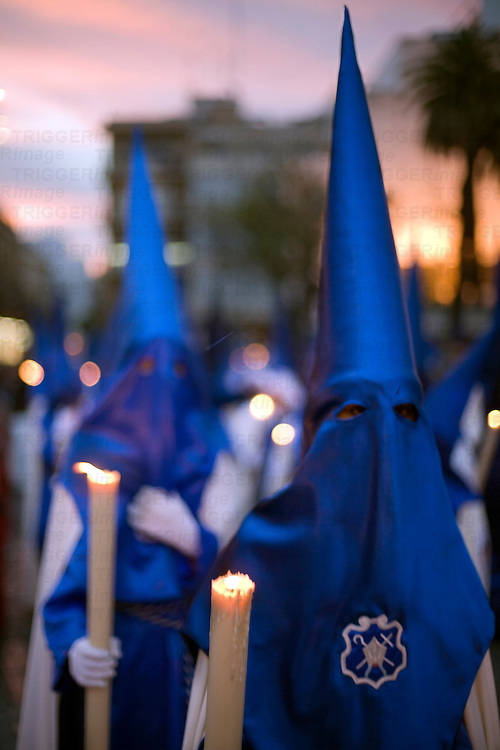 Hooded penitents bearing candles at dusk, Holy Week, Seville, Spain
