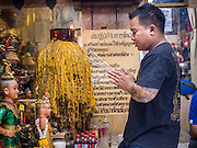 "25 MAY 2015 - BANGKOK, THAILAND:  One of Ajarn Neng Onnut's tattoo assistants prays before a day of tattooing starts in Ajarn Neng's tattoo parlor. Sak Yant (Thai for ""tattoos of mystical drawings"" sak=tattoo, yantra=mystical drawing) tattoos are popular throughout Thailand, Cambodia, Laos and Myanmar. The tattoos are believed to impart magical powers to the people who have them. People get the tattoos to address specific needs. For example, a business person would get a tattoo to make his business successful, and a soldier would get a tattoo to help him in battle. The tattoos are blessed by monks or people who have magical powers. Ajarn Neng, a revered tattoo master in Bangkok, uses stainless steel needles to tattoo, other tattoo masters use bamboo needles. The tattoos are growing in popularity with tourists, but Thai religious leaders try to discourage tattoo masters from giving tourists tattoos for ornamental reasons.       PHOTO BY JACK KURTZ"