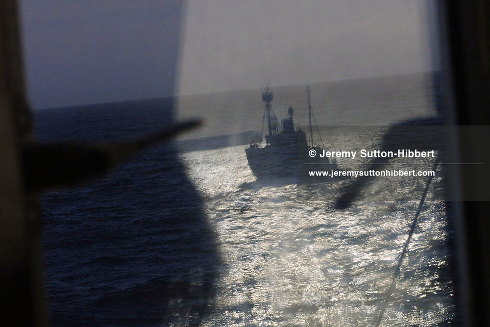 A Japanese whale catcher ship is reflected in a window of the MV Arctic Sunrise, a ship belonging to the enviromental protest group 'Greenpeace'.  The Greenpeace ship is in the Southern Ocean to protest against the Japanese commercial whaling of Antarctic Minke whales, tand to ask them to cease whaling and to return to Japan. The Japanese whaling fleet consists of 5 ships, and will hunt and kill 440 Antarctic Minke whales in their annual expedition to the Southern Ocean..