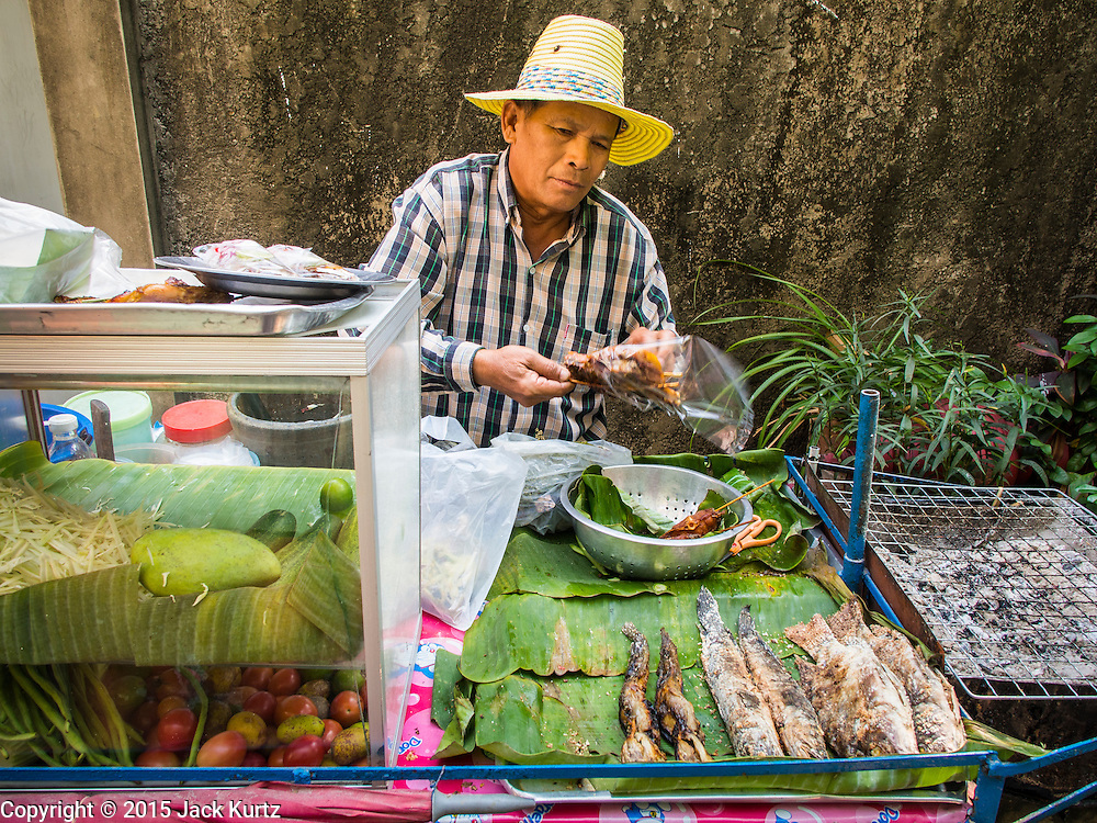 06 FEBRUARY 2015 - BANGKOK, THAILAND: A street food vendor bags an order of grilled chicken in the neighborhood around Santa Cruz Church in the Thonburi section of Bangkok. He makes and sells spicy mango salad, grilled chicken and grilled fish on his push cart. Now the neighborhood around the church is known for the Thai adaptation of Portuguese cakes baked in the neighborhood. Several hundred Siamese (Thai) Buddhists converted to Catholicism in the 1770s. Some of the families started baking the cakes. When the Siamese Empire in Ayutthaya was sacked by the Burmese, the Portuguese and Thai Catholics fled to Thonburi, in what is now Bangkok. The Portuguese established a Catholic church near the new Siamese capital. There are still a large number of Thai Catholics living in the neighborhood around the church.       PHOTO BY JACK KURTZ