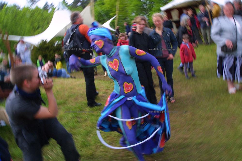 """Eine junge Frau, die von einer Bodypainterin am ganzen Körper bemalt wurde, tanzt als lebendiges Kunstwerk durch die Besucher einer Veranstaltung der Kulturellen Landpartie im Wendland. Die """"Kulturelle Landpartie"""" zieht jedes Jahr tausende Kunst- und Kulturinteressierte aus ganz Deutschland an, die auf den unzähligen Veranstaltungen und Ausstellungen im Wendland dabei sein wollen."""