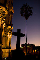 A cross and a palm tree are see at the Parochial church of San Miguel Arcángel on Christmas eve at sunset in San Miguel de Allende, Mexico