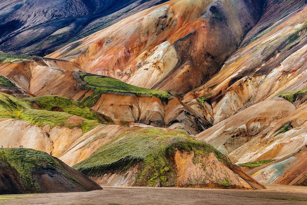 People hikin the lower lava drainages in the rhyolite hills of Landmannalaugar National Park in Iceland.