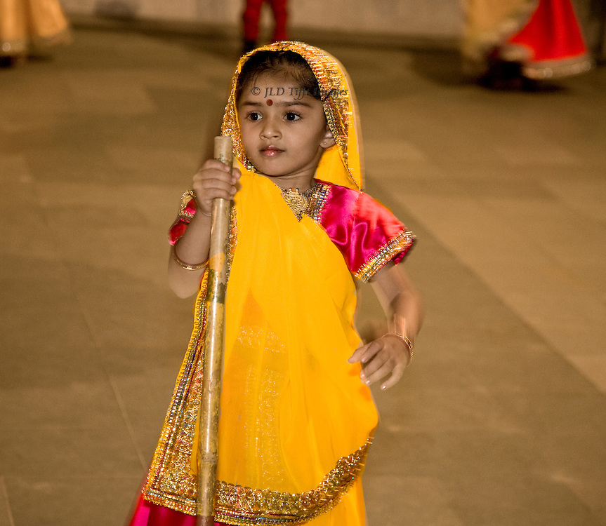 Little girl about 5 years old in traditional costume performs a Gujarati stick dance.