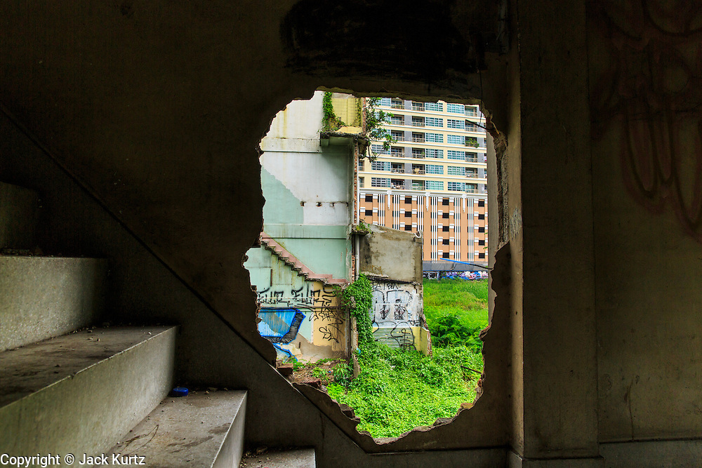 16 OCTOBER 2012 - BANGKOK, THAILAND:  Looking out of a hole in the wall of an abandoned building on Phetchaburi Rd in central Bangkok, Thailand. The building used to be an optician's shop with residences above the ground floor shop. The global economic slowdown had little visible effect in Bangkok. Construction projects dot the city of 12 million and development continues unabated.   PHOTO BY JACK KURTZ