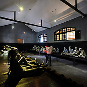 Two tourists walk through a room demonstrating the rooms that the general prison population was kept in at Hoa Lo Prison, with plastic sculptures representing the prisoners shackled by one leg into irons running the length of each side of the room. Hoa Lo Prison, also known sarcastically as the Hanoi Hilton during the Vietnam War, was originally a French colonial prison for political prisoners and then a North Vietnamese prison for prisoners of war. It is especially famous for being the jail used for American pilots shot down during the Vietnam War.