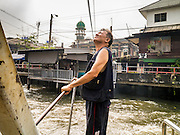21 NOVEMBER 2012 - BANGKOK, THAILAND:  The mechanic inspects the cable that pulls a small pedestrian ferry across Khlong Saen Saeb in Bangkok. There are only a few ferries that cross the Khlong. They use a winch to pull the boat across the Khlong. The fare is 2 Thai Baht, about $0.10 (US). Bangkok used to be criss crossed by canals (called Khlongs in Thai) but most have been filled in and paved over. Khlong Saen Saeb is one of the few remaining khlongs in Bangkok with regular passenger boat service. Khlong Saen Saeb was dug in 1837 to be a military supply line from Bangkok to Siamese armies battling Annamese (now Vietnamese) forces in what is now Cambodia. Boats and ships play an important in daily life in Bangkok. Thousands of people commute to work daily on the Chao Phraya Express Boats and fast boats that ply Khlong Saen Saeb. Boats are used to haul commodities through the city to deep water ports for export.   PHOTO BY JACK KURTZ