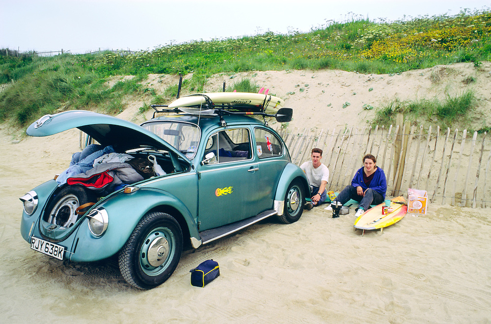 Young couple preparing to surf on the surfing beach at Newquay, Cornwall, England. VW Beetle.