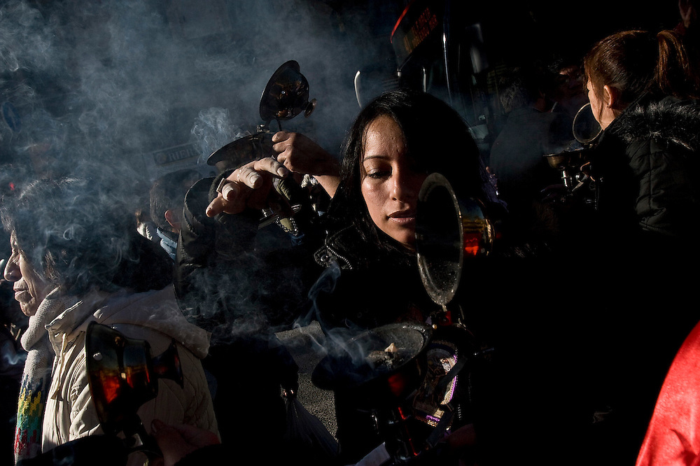 Latin American Immigrants in Barcelona.<br /> A &quot;ahumadora&quot; lights incense during the peruvian religious prosecion called: &quot;El Cristo de los Milagros&quot; (the Christ of the Miracles) in El Raval in Barcelona. Every year since 1994 the peruvian collective hosts this procession in Barcelona, not just in honor of the story of this crucifix, that miraculously survived an earthquake in Per&uacute; in the XVIII century, but also in memory of the peruvian culture and country.
