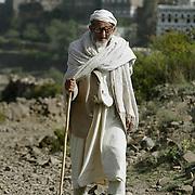 An old Yemeni men takes a walk outside of the mountain village of Kahel in the Haraz mountains near Al Hajjarah.