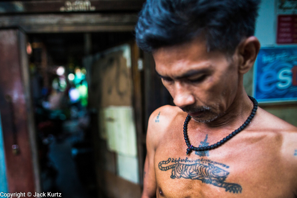 "13 JANUARY 2013 - BANGKOK, THAILAND:  A man with a ""sak yant"" or holy tiger tatoo on his chest in front of his home in the Bang Luang neighborhood of Bangkok. He believes the tattoo enables him to channel the power of the tiger. The Bang Luang neighborhood lines Khlong (Canal) Bang Luang in the Thonburi section of Bangkok on the west side of Chao Phraya River. It was established in the late 18th Century by King Taksin the Great after the Burmese sacked the Siamese capital of Ayutthaya. The neighborhood, like most of Thonburi, is relatively undeveloped and still criss crossed by the canals which once made Bangkok famous. It's now a popular day trip from central Bangkok and offers a glimpse into what the city used to be like.     PHOTO BY JACK KURTZ"