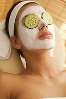 Young woman lying down on massage table with cucumbers on eyes