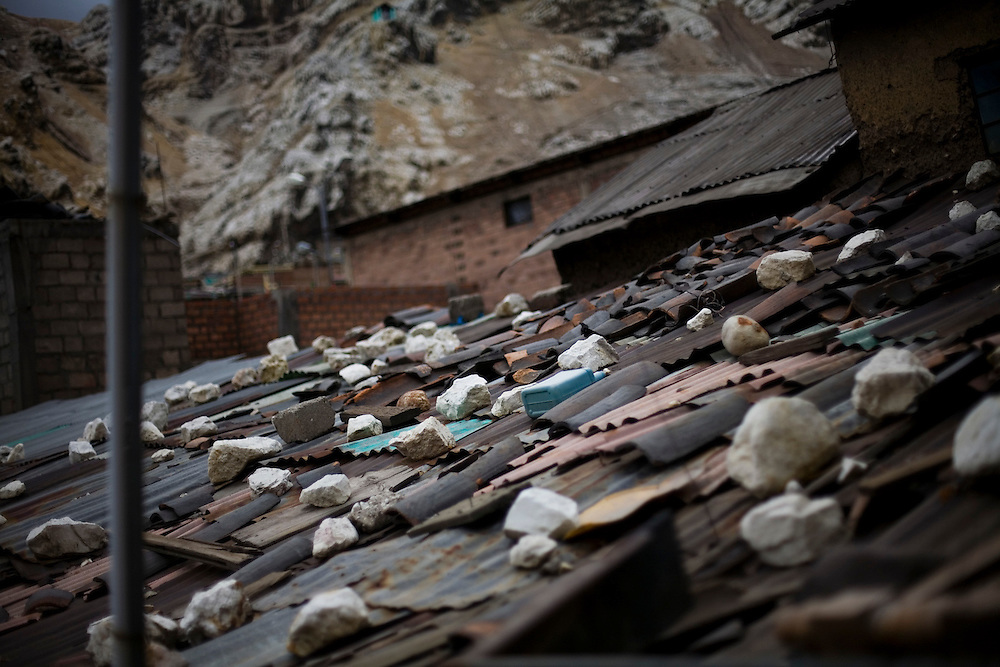 Rocks weigh down a corrugated tin roof to keep it from blowing away. The majority of people in La Oroya live in extreme poverty.