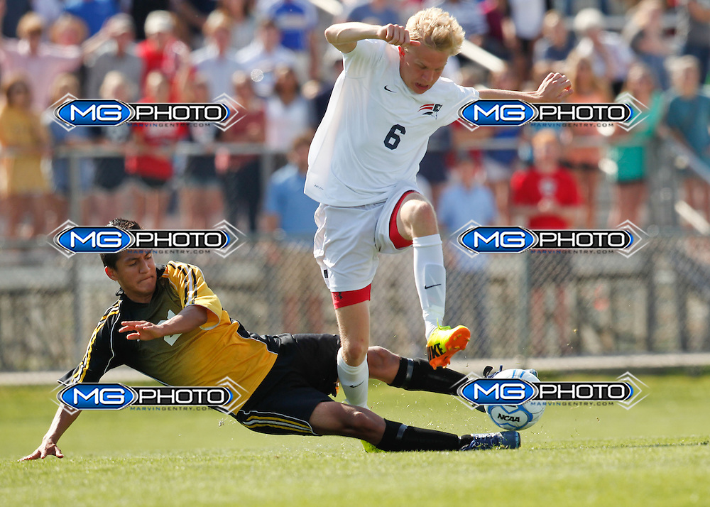 May 10, 2014; Huntsville, AL, USA; Homewood Ian Ross (6) is tripped up by Fort Payne Luis Carrizal (21) during the 5A Boys State Soccer Championship at John Hunt Soccer Complex. Mandatory Credit: Marvin Gentry
