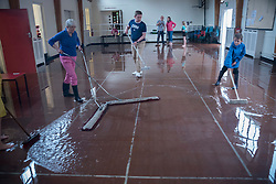© Licensed to London News Pictures. 23/06/2016. London, UK. Members of the congregation use brooms to sweep away floodwater in Emmanuel church hall after a torrential rain shower lasting for more than 30 minutes causes localised flooding in Northwood, north west London. Photo credit : Stephen Chung/LNP