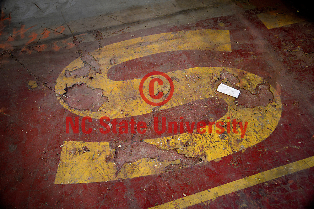 "Discolored, once white ""S"" on the end zone of the old Reynolds Coliseum floor."