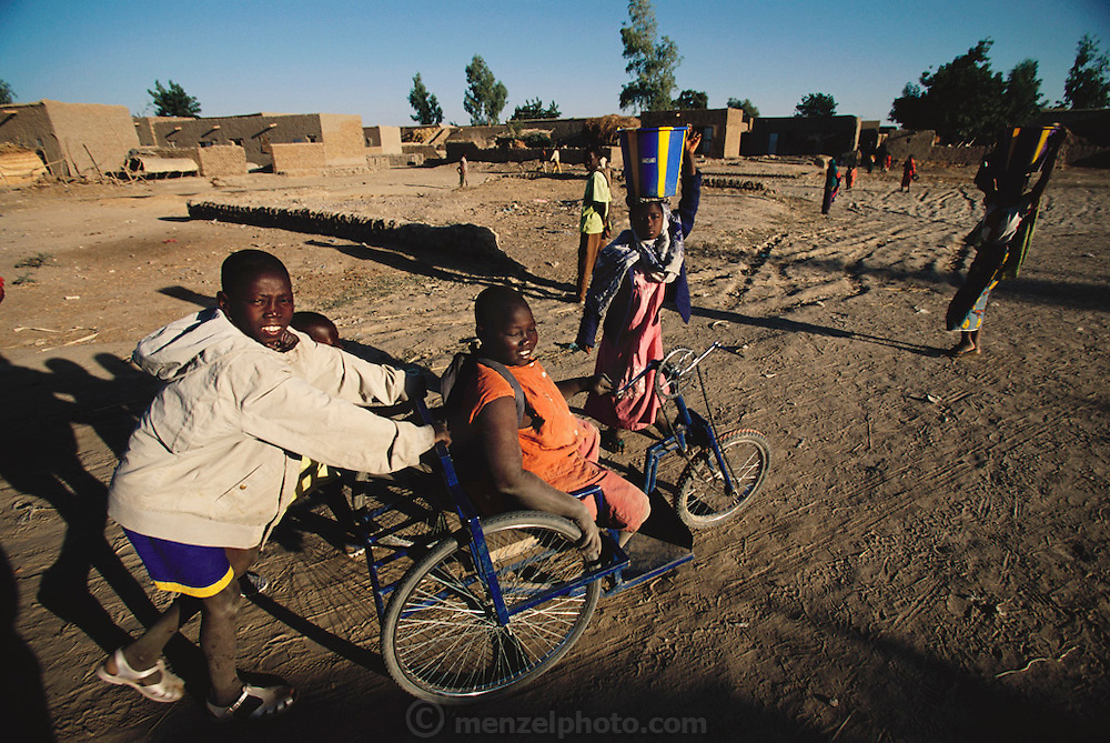 Disabled boy gets a helpful push on his tricycle wheelchair from a friend on the way to school in the village of Kouakourou, Mali.