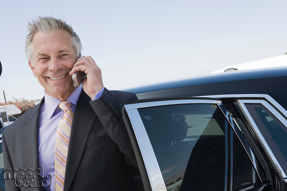 Portrait of senior businessman standing in front of limousine and talking on phone.