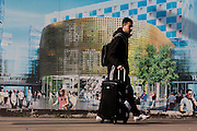 A utopian view of a Londoner passing a hoarding showing aspiration and consumerism of nearby Westfield City shopping complex, Stratford. Situated on the fringe of the 2012 Olympic park, Westfield hosted its first day to thousands of shoppers eager to see Europe's largest urban shopping centre. The £1.45bn complex houses more than 300 shops, 70 restaurants, a 14-screen cinema, three hotels, a bowling alley and the UK's largest casino. It will provide the main access to the Olympic park for the 2012 Games and a central 'street' will give 75% of Olympic visitors access to the main stadium so retail space and so far 95% of the centre has been let. It is claimed that up to 8,500 permanent jobs will be created by the retail sector.