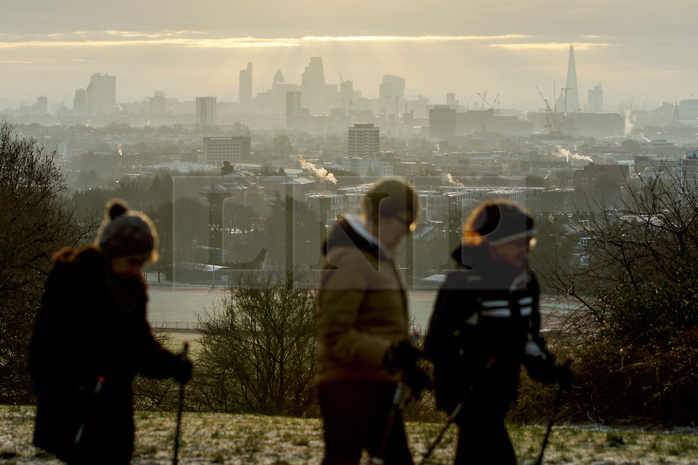 © Licensed to London News Pictures. 06/01/2017. London, UK. People hike whilst sunrise is seen over the city of London from Parliament Hill on Hampstead Heath in north London on a cold winter morning of Friday, 6 January 2016. Photo credit: Tolga Akmen/LNP