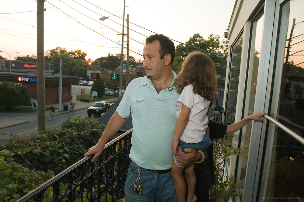 Ramsi Kamar, owner of Ramsi's Cafe on the World, photographed on a balcony in his family's apartment above the restaurant Friday, Sept. 11, 2009 on Bardstown Road in Louisville, Ky. Ramsi holds his daughter Safi, 4, as his son Nizar, 10, looks on. His wife Roni and other daughter Graciella, 11, are not shown. (Photo by Brian Bohannon)