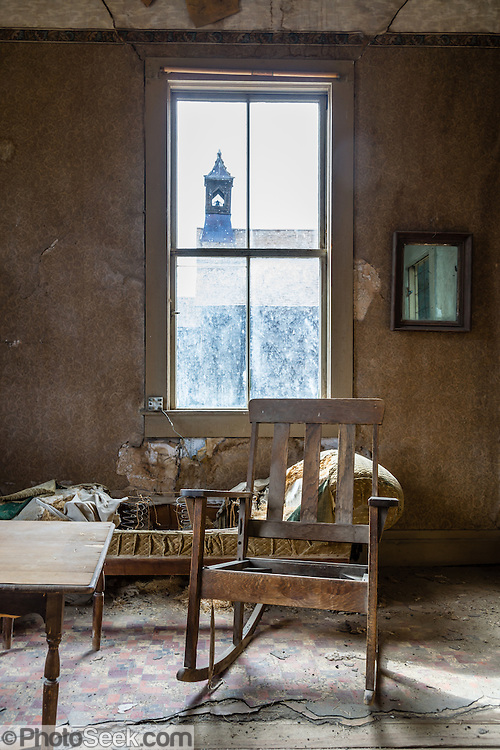 "An old rocking chair in the ramshackle Miller House sits by a window looking out to the Methodist Church at Bodie, California's official state gold rush ghost town. Bodie State Historic Park lies in the Bodie Hills east of the Sierra Nevada mountain range in Mono County, near Bridgeport, California, USA. After W. S. Bodey's original gold discovery in 1859, profitable gold ore discoveries in 1876 and 1878 transformed ""Bodie"" from an isolated mining camp to a Wild West boomtown. By 1879, Bodie had a population of 5000-7000 people with 2000 buildings. At its peak, 65 saloons lined Main Street, which was a mile long. Bodie declined rapidly 1912-1917 and the last mine closed in 1942. Bodie became a National Historic Landmark in 1961 and Bodie State Historic Park in 1962."