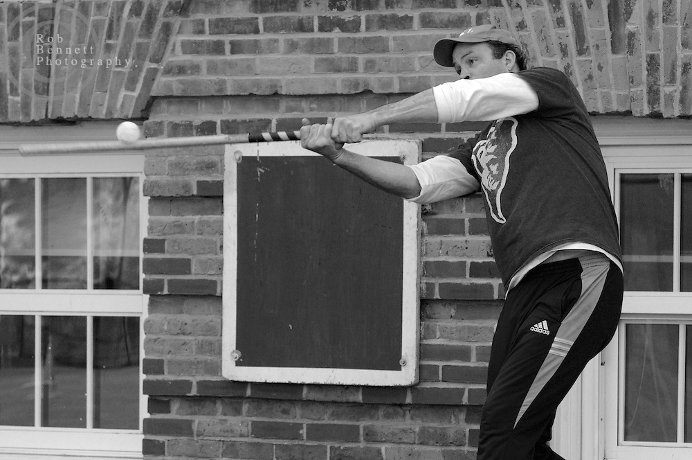 "Andy Ettinger, 49 and an independent bookseller from Hastings-on-Hudson, bats during a game of stickball..---.The Ethical Stickball League has been operating since 1970, meeting every Sunday in the parking lot behind Hastings High School from 10:30AM to 1PM.  The players are men now mostly in their 70s - carrying nicknames like ""The Wise One"", ""Hit Man"" and ""Plays Hurt"" - who have an affiliation with the school, either as former teachers, students or neighbors. As their slogan suggests, all it takes for a few hours of ""Aestas Aeterna"" (Eternal Summer) is an outside temperature above 45 degrees and 8 willing souls...CREDIT: Rob Bennett for The NY Times"