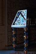 Reflection of a stained glass window in a cabinet with legs of blue and gold glass beads by Murano glassmaker Salviati, in the Bell tower room themed 'Le Merveilleux' or The Supernatural, first floor, in Le Tresor de la Cathedral d'Angouleme, in Angouleme Cathedral, or the Cathedrale Saint-Pierre d'Angouleme, Angouleme, Charente, France. The 12th century Romanesque cathedral was largely reworked by Paul Abadie in 1852-75. In 2008, Jean-Michel Othoniel was commissioned by DRAC Aquitaine - Limousin - Poitou-Charentes to display the Treasure of the Cathedral in some of its rooms, which opened to the public on 30th September 2016. Picture by Manuel Cohen. L'autorisation de reproduire cette oeuvre doit etre demandee aupres de l'ADAGP/Permission to reproduce this work of art must be obtained from DACS.