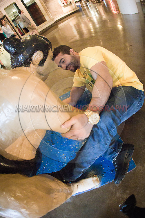 "ST. LOUIS, MO, JUNE 16, 2015: Patricio ""Pitbull"" Freire sweeps the leg of a sumo statue inside City Museum ahead of his fight at Bellator 138 in St. Louis, Missouri © Sara Levin"
