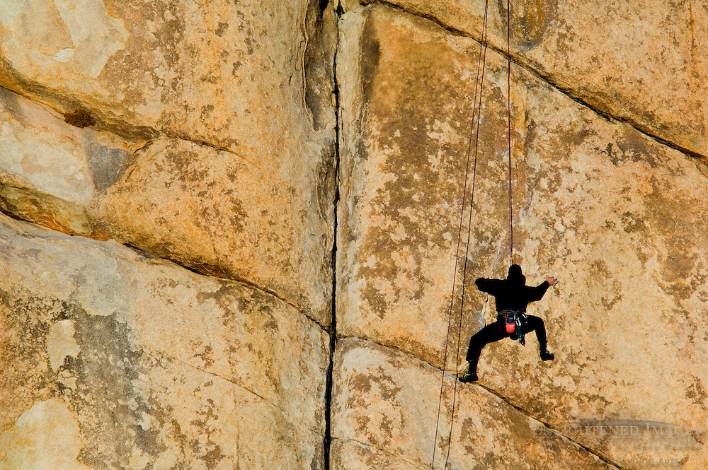 Rock climber climbing at Hidden Valley, Joshua Tree National Park, California