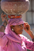 Indian woman in sari fetching water pots from well at Jawali village in Rajasthan, Northern India