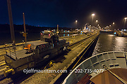 A ship transits Gatun Locks with the aid of a mule on the Panama Canal at night.
