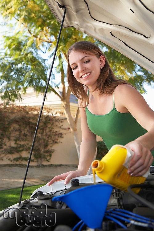 Young woman pouring oil into car engine