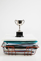 Trophy over stack of folders against white background