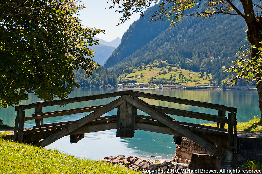 Romantic wooden bridge on the lake in Le Pese, Graubunden, Switzerland.