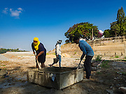 21 JANUARY 2016 - KHLONG PHAI, NAKHON RATCHASIMA, THAILAND: Maintenance workers repair the spillway  at Lam Takhong Dam in Nakhon Ratchasima province. The dam is only 30 percent of its capacity and farmers downstream have been told they can't draw irrigation water from the dam.  The drought gripping Thailand was not broken during the rainy season. Because of the Pacific El Nino weather pattern, the rainy season was lighter than usual and many communities in Thailand, especially in northeastern and central Thailand, are still in drought like conditions. Some communities, like Si Liam, in Buri Ram, are running out of water for domestic consumption and residents are traveling miles every day to get water or they buy to from water trucks that occasionally come to the community. The Thai government has told farmers that can't plant a second rice crop (Thai farmers usually get two rice crops a year from their paddies). The government is also considering diverting water from the Mekong and Salaween Rivers, on Thailand's borders to meet domestic needs but Thailand's downstream neighbors object to that because it could leave them short of water.     PHOTO BY JACK KURTZ
