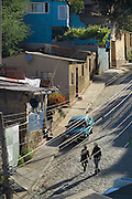Couple walking holding hands in neighborhood of Valparaiso, Chile