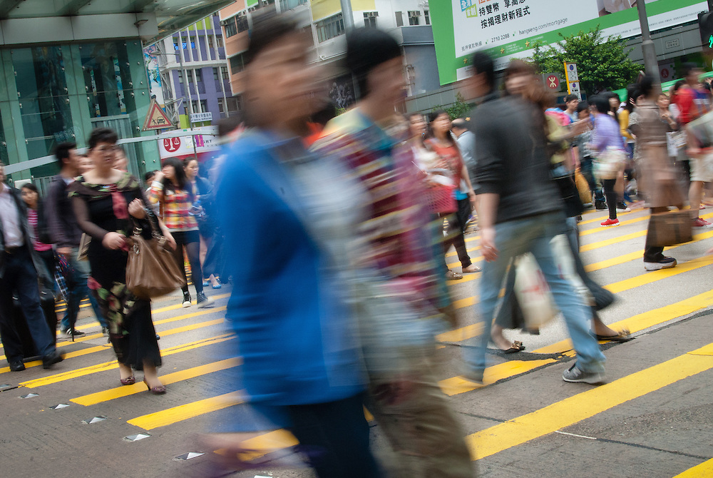 Crossing at a busy intersection on Nathan Road in the shopping district of Mong Kok, Hong Kong