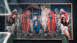 "© Licensed to London News Pictures. 22/10/2018. LONDON, UK. A staff member stands next to ""The Adoration of the Magi"", 1894, by Edward Burne-Jones.  Preview of the largest Edward Burne-Jones retrospective to be held in a generation at Tate Britain.  Burne-Jones was a pioneer of the symbolist movement and the only Pre-Raphaelite to achieve world-wide recognition in his lifetime.  The exhibition runs 24 October to 24 February 2019.  Photo credit: Stephen Chung/LNP"