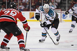 Oct 21; Newark, NJ, USA; San Jose Sharks center Logan Couture (39) skates with the puck while being defended by New Jersey Devils defenseman Anton Volchenkov (28) during the first period at the Prudential Center.