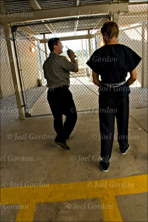 Correction Officer taking handcuffed inmate back to jail cell block