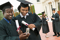 Two Friends at Graduation Using Cell Phone